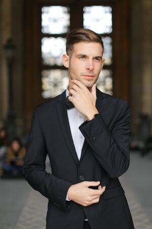 Young caucasian man standing and waiting, wearing black suit and bow tie, window in background. Concept of fashionable businessman and male model.