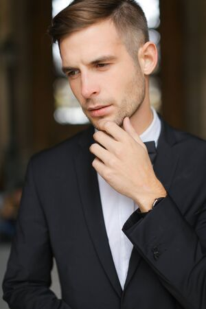 Portrait of young man wearing black suit with bow tie and white shirt. Concept of male groom model.
