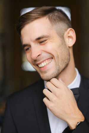 Portrait of young smiling man wearing black suit with bow tie and white shirt. Concept of male model.