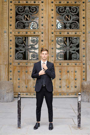 Handsome cauasian groom standing near wooden door and straightening tie, wearing black suit. Concept of male fashion.