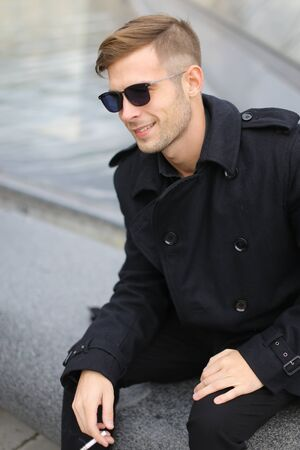 Young smiling man in sunglasses wearing black jacket sitting near glass Louvre Pyramid in Paris and smoking cigarette, France. Concept of male fashion model and urban photo session.