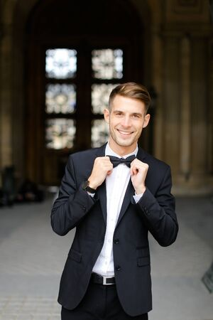 Young european man standing and posing, wearing black suit and bow tie, window in background. Concept of fashionable businessman and male model.