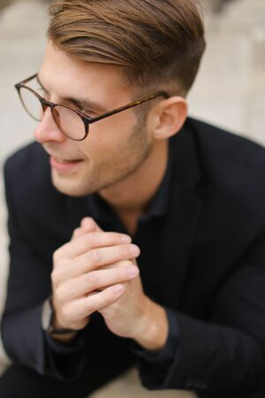 Closeup portrait of handsome male person wearing black suit and glasses. Concept of fashionable model.