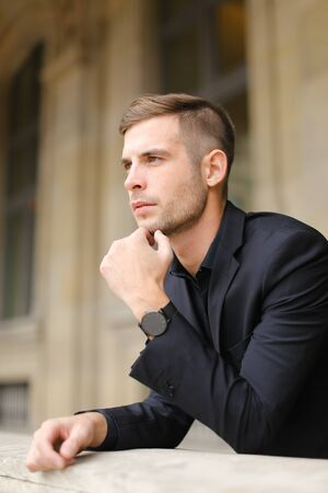 Closeup portrait of young businessman on balcony leaning on banister. Concept of male model and fashion. Young man wearing black suit. Standard-Bild