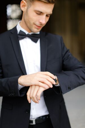 Young handsome man wearing black suit and waiting, loking at watch. Concept of male model and businessman.