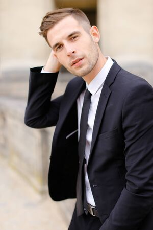 Portrait of handsome man wearing black suit and leaning on concrete banister. Concept of of waiting groom and male wedding photo session.