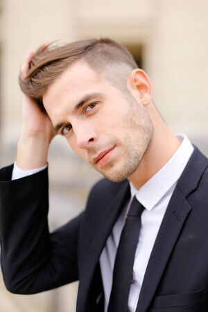 Closeup portrait of young caucasian man wearing balck suit and tie. Concept of male fashionable model and groom photo session. Standard-Bild