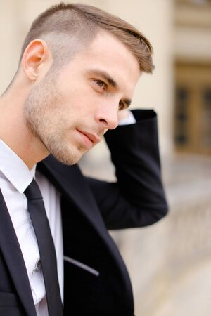 Closeup portrait of young handsome caucasian man wearing balck suit and tie. Concept of male fashionable model and groom photo session. Standard-Bild