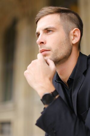 Closeup portrait of young man wearing black suit and watch. Concept of successful businessman and male model.