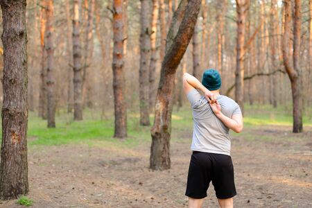 Back view of young boy doing morning exercises in park. Concept of workout and health. Man resting in spring forest.