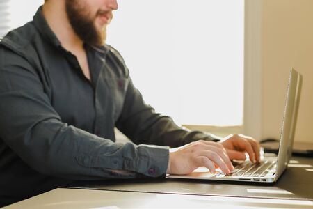 Male manager working with laptop in office, searching ideas, sitting at desk. Concept of modern technology and business. Bearded man surfing internet. Standard-Bild