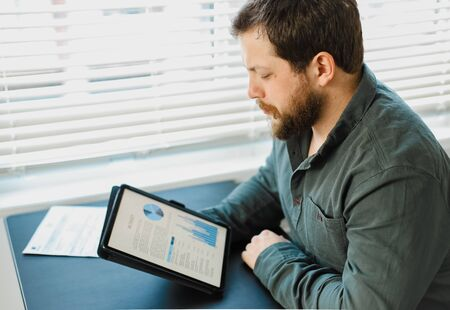 European male engineer working with graphs and diagrams on tablet at office. Concept of professional occupation and smart employee. Adult man surfing internet by modern gadget.