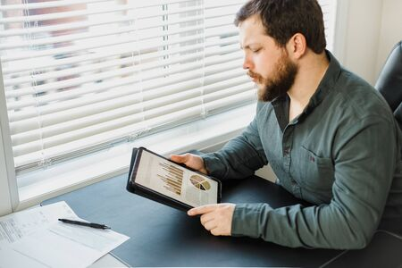 Male marketolog working with graphs and diagrams on tablet at office. Concept of professsional occupation and smart employee. Adult bearded man wearing shirt and surfing internet at cabinet.