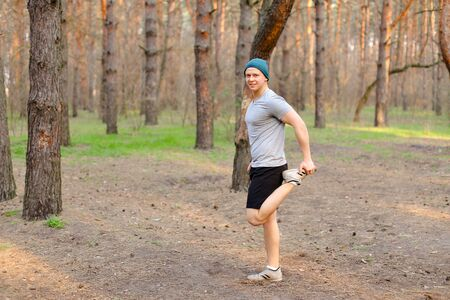 Young caucasian boy doing stretch marks in park morning. Concept of workout on nature and fitness exercises. Man wearing cap and grey t shirt resting in spring forest. Banco de Imagens - 147249847