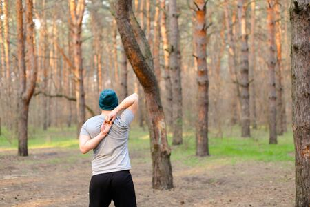 Back view of boy doing morning exercises in park. Concept of workout and health. Man resting in spring forest. Standard-Bild
