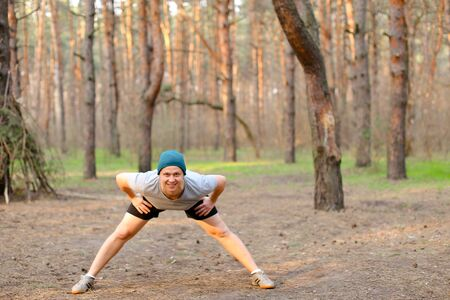 Young adult boy doing stretch marks in park morning. Concept of workout on nature and fitness exercises. Man wearing cap and grey t shirt resting in spring forest.