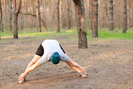 Young male caucasian person doing stretch marks in morningpark. Concept of workout on nature and fitness exercises. Man wearing cap and grey t shirt resting in spring forest. Banco de Imagens - 147251833