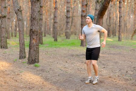 Young man jogging and running in morning park on fresh air. Concept of fitness and health. Guy wearing cap and grey t shirt resting in spring forest.
