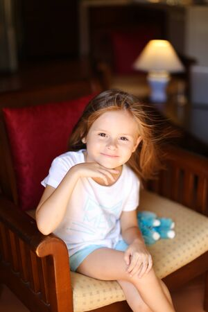 Little beautiful female kid sitting with toy in wooden chair. Concept of kid model and wood in interior.