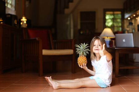 Little smiling female kid sitting on floor in living room with pineapple and showing thumbs up, laptop in background. Concept of health life, fruit and childhood.