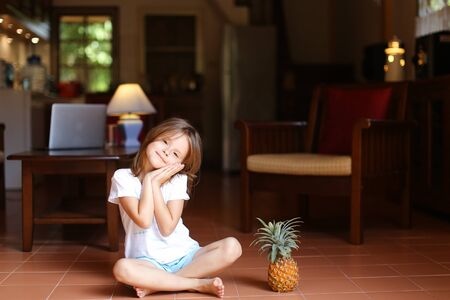 Little female kid sitting on floor in living room and keeping pineapple, laptop in background. Concept of health life, fruit and childhood. Standard-Bild