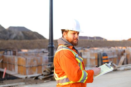 Caucasian inspector in orange workwear with blueprints and notebook on construction site. Concept of builder profession and foreman . Standard-Bild