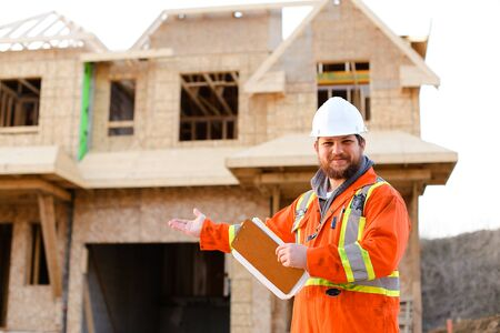 European architect in orange workwear holding notebook on construction site, house in background. Concept of real estate in Europe.