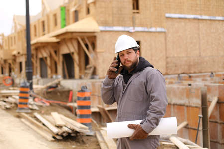 Builder talking by mobile phone and holding drawing plan at construction site, wearing hardhat. Concept of architectural profession and house building. Stock Photo