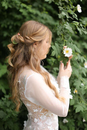Profile portrait of blonde bride without vail in green plant background.
