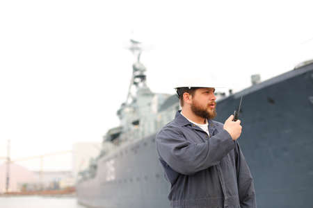 Captain wearing helmet and talking by VHF walkie talkie radio, standing on coast with offshore vessel in background. Concept of maritime job and engineering department of marine team.