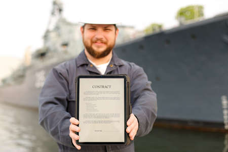 Focus on contract, marine captain showing document on tablet near vessel in background. Concept of maritime profession and modern technology.