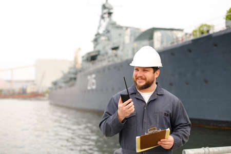 European first mate wearing helmet and talking by VHF walkie talkie radio, holding papers documents, standing on coast near vessel. Concept of maritime job and engineering department of marine team.