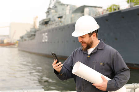 Marine happy engineer speaking by VHF walkie talkie, holding blueprints near vessel in background, wearing helmet and work jumpsuit. Concept of maritime profession , job and seaman.