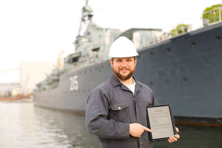 Captain in helmet showing contract on electronic book or tablet near vessel in background. Concept of maritime profession and modern technology. Archivio Fotografico