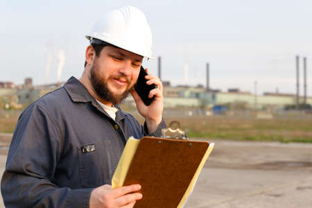 Portrait of european foreman standing on construction site, speaking by VHF walkie talkie and holding papers. Man wearing white helmet and work jumpsuit. Concept of industry profession and building engineering job.