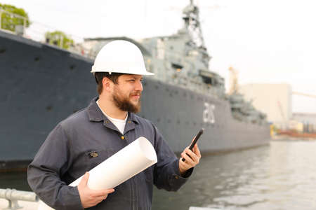 Marine engineer speaking by VHF walkie talkie, holding blueprints near vessel in background, wearing helmet and work jumpsuit. Concept of maritime profession , job and seaman.