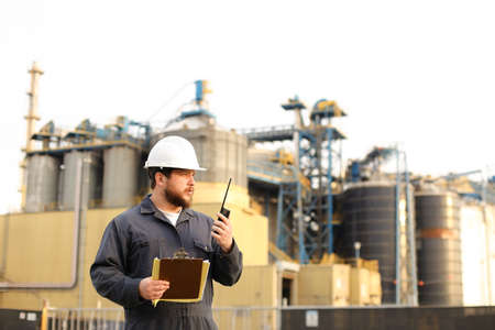 Caucasian american engineer holding VHF walkie talkie and notes, factory in background. Concept of engineering profession and modern technology, worker. Stock Photo