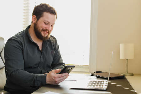 Successfel enterpreneur working with laptop and smartphone at ofice. Concept of developing own business and modern technology. Bearded adult man surfing internet.