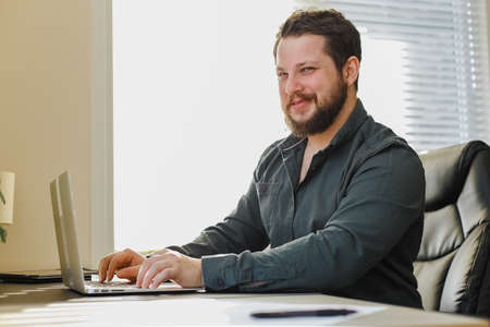 Caucasian male manager sitting at office desk working on laptop computer. Concept of modern technology and occupation. Bearded man surfing internet.