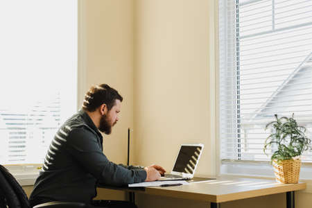 Male manager sitting at desk and working with laptop at office. Concept of modern technology and business director of company. Bearded man using gadgets and surfinhg internet. 免版税图像