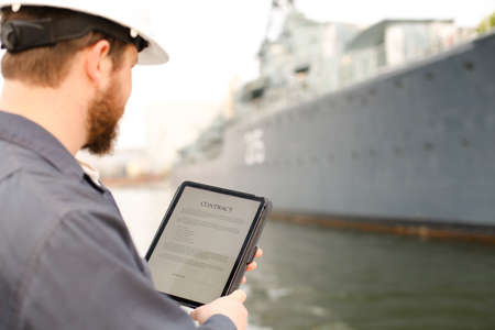 Captain reading contract on electronic book or tablet near vessel in background. Concept of maritime profession and modern technology.