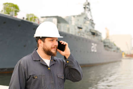 Marine captain speaking by VHF walkie talkie near vessel in background, wearing helmet and work jumpsuit. Concept of maritime profession , job and seaman. Stock Photo