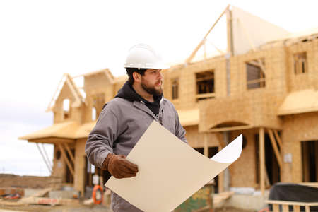 Builder holding architectural drawing plan on paper at construction site and wearing hardhat. Concept of blueprint, architecture and house building. Banco de Imagens