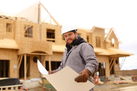 Bearded builder holding architectural drawing plan on paper at construction site and wearing hardhat. Concept of blueprint, architecture and house building.