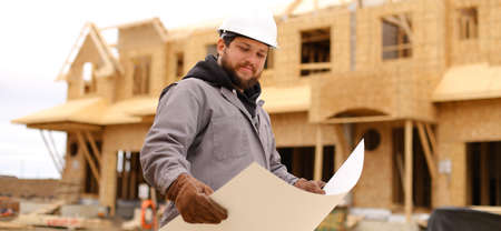 Banner of builder holding architectural drawing plan on paper at construction site and wearing hardhat. Concept of blueprint, architecture and house building.