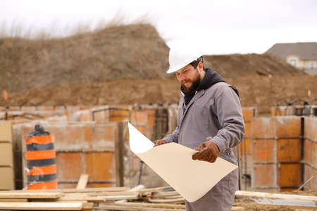 Male foreman looking at drawing plan of hause at construction site, wearing white hardhat. Concept of hause building and builder profession.