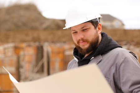 Portrait of male architect holding drawing plan of hause at construction site, wearing white hardhat. Concept of hause building and builder profession. Banco de Imagens