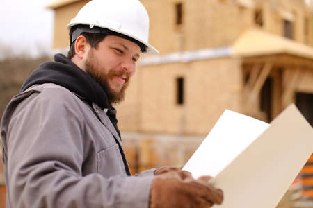 Portrait of male foreman holding drawing plan of hause at construction site, wearing white hardhat. Concept of hause building and builder profession.