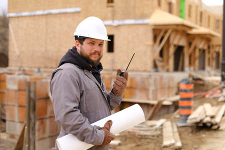 Architect talking by walkie talkie and holding drawing plan at construction site, wearing hardhat. Concept of architectural profession and house building. Banco de Imagens