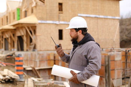Architect speaking by walkie talkie and holding drawing plan at construction site, wearing hardhat. Concept of architectural profession and house building.